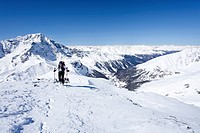 Touring skier climbing to the top of Hintere Schoentaufspitze mountain, Sulden in winter, Ortler mountain and Suldental valley at the back, province o...