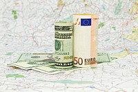 Two currencies, dollar and euro, placed on a map indicate the shared nature and dependencies within a global economy´s market and financial system.