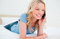 Woman smiling as she makes a call looking ahead of her