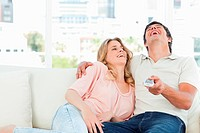 Man and woman on the couch laughing at the tv programme