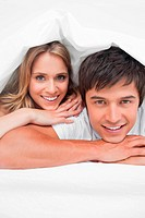 Close up, man and woman smiling and resting on their hands at the end of the bed
