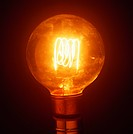 Incandescent light bulb filament. Glowing tungsten filament center inside an incandescent light bulb. A light bulb produces light from a heated tungst...