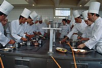 A number of cooks at work in a busy restaurant kitchen.