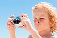 Boy taking pictures at the beach