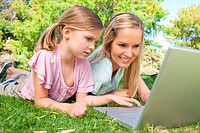 Mother and daughter using the laptop together in the park