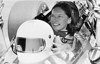 Portrait of race car driver Janet Guthrie preparing for a test race before the 1976 Trentonian 200.