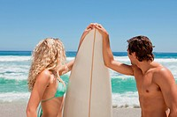 Young couple holding a surfboard on the beach while looking at the sea