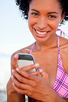 Smiling young woman looking at the camera while sending a text