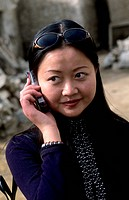 Young modern business woman on cell phone in rural Tibet.