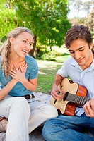 Man impressing his girlfriend by playing a guitar