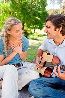 Woman listening to her guitar playing boyfriend