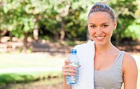 Smiling sportswoman with a towel and a bottle of water