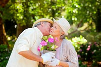 Man kissing a woman while exchanging a pot of flowers