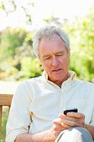 Man with a serious expression using a phone while sitting on a bench
