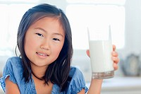 Close up of a girl with a glass of milk in hand