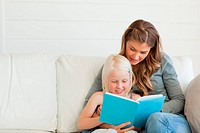 Mother and daughter sitting on the couch reading together