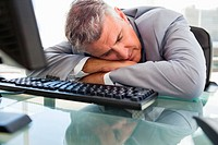 Businessperson sleeping on his desk