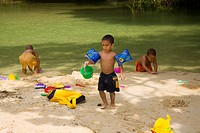 Children play on a sandy beach in Jamaica.