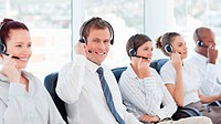 Smiling call center agent sitting in between his colleagues