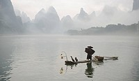 Traditional Chinese fisherman with cormorants, on Li River, near Xingping, China. The Li River is famous for the karst mountains along its banks.