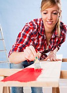 Young woman painting a board with a brush
