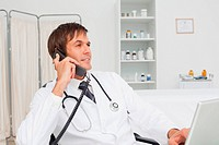 Relaxed doctor sitting at his desk while talking on the phone