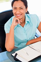 Smiling secretary placing her hand on her chin while working