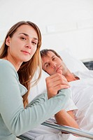 Relaxed woman holding the hand of her husband in a hospital room