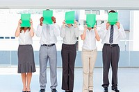 Business team holding green sheets in front of their face