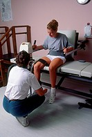 Physical therapist works with patient using a cybex machine to strengthen knee muscles.
