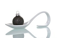 Christmas bauble on a serving spoon, symbolic image for Christmas dinner