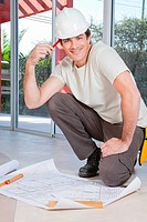 Smart young construction worker smiling with blueprint on floor