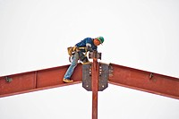 An ironworker assembles the steel frame of a public building in Southern California. Note hard hat and other safety equipment.