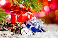 gift boxes and clock on snow with christmas tree branch on blurred background