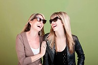 Happy Caucasian mom and daughter with sunglasses laugh together