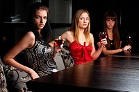 Young women sitting in cafe with wine and talking