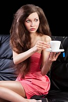 sophisticated young pretty brunette in pink elegant dress sitting on a black sofa and tasting a cup of tea. she looks at left and takes one cup of tea...
