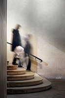 Two people in blurred motion walking down ancient staircase