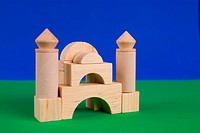 Wood toy block castle on the blue and green background