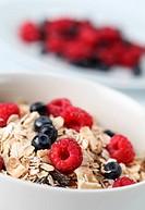 Granola with fresh organic raspberries and blueberries. Shallow DOF