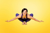 young woman exercise yoga arm balance in blue on yellow