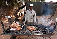 Man is selling a roast chicken on the street in a small town in RSA