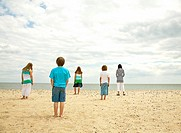 Children standing on empty beach