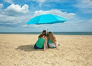 Sisters sitting under umbrella on beach