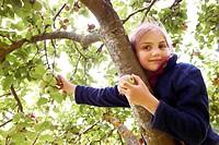 Smiling girl picking fruit from tree