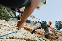 Climbers scaling steep rock face