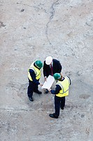 Workers reading blueprints at dry dock