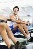 Couple using rowing machines in gym
