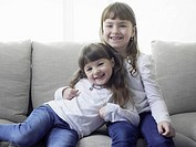 Smiling girls sitting on sofa together