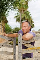 Man leaning on wooden fence outdoors